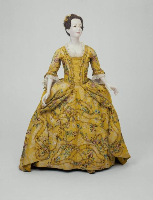 Dress, ca 1745 (restyled ca 1760) England, the Museum of Fine Arts, Boston  Yellow silk brocaded with polychrome silks in floral motifs. Robe: neck and front lines with matching bands of ruching; sack (Watteau) back with stitched-down pleats; short fitted sleeves with double asymmetrical ruffles; panier accomodating skirt with slits at hipline, fullness knife-pleated into waistline; linen bodice lining. Underskirt: fullness pleated into tie-tape waistband; scallped ruffle and ruching in ribbon motif applied to front.