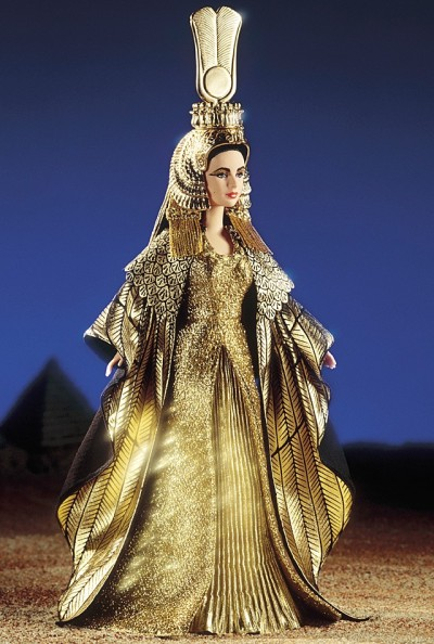 "suffragettebarbie:  Elizabeth Taylor in Cleopatra™ Elizabeth Taylor as Cleopatra — her magnificent golden costume is re-created here in splendid detail. Cleopatra's luxurious gown has a dramatic ""feather"" cloak that surrounds her like the wings of a bird. Her spectacular headdress features cobra symbols that protect royalty, a sun disk enclosed in horns, identifying her with the goddess Isis, and a large double feather representing cosmic harmony.The meticulous sculpting of our Cleopatra doll captures the stunning likeness of Elizabeth Taylor. Her face is painted so realistically that every detail is authentic to the movie - from the incredibly fine glitter eye shadow and heavy kohl liner to the exact shade of violet for her eyes. She is an amazing tribute to Elizabeth Taylor in one of her most glamorous roles."