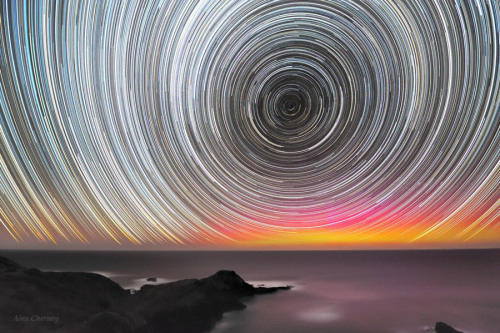 ikenbot:  Aurora Australis Between the Ocean & Star trails  Southern lights or the Aurora Australis above the ocean and under the trails of stars, as photographed from Mornington Peninsula, not far from Melbourne, Australia. — Alex Cherney