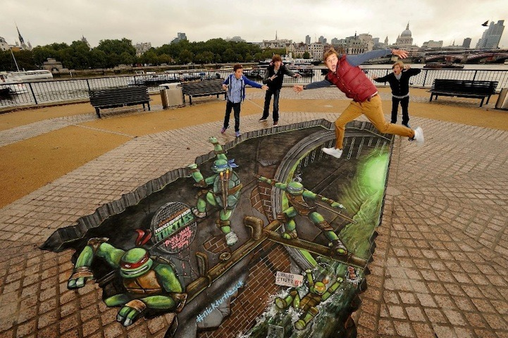 "Joe and Max is the Creative Company behind a multitude of 3d paintings that help promote for such ventures as The Dark Knight Returns, Nightfall and a plethora of great creative ventures. Their latest piece ""breaks open""  the streets at London's Southbank to reveal those crime-fighting Teenage Mutant Ninja Turtles playing and crawling their way out of the sewers. A combination of paint and chalk, the unbelievably awesome piece took them about 50 hours to complete. Made to promote the release of the all-new Teenage Mutant Ninja Turtles animated TV series on Nickelodeon, the artwork drew young and old alike who interacted with it in as slew of creative ways."