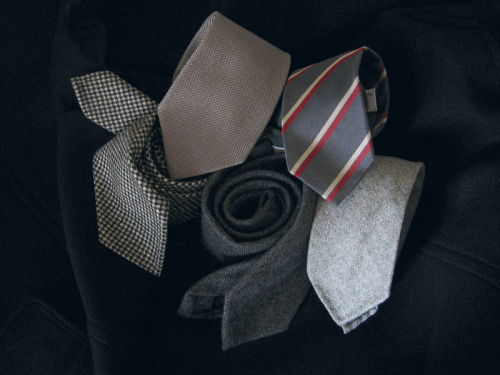 The Silver Necktie Commonly recommended colors for neckties include the darker shades of blue, brown, green, and red, but rarely do you see mentions of silver or grey. Silver or grey, however, are some of the best colors you can wear with navy suits. And while fewer and fewer men have the occasion to wear suits these days, when they do, navy is a good stand-by, so having a few silver or grey neckties on hand is a good idea. For formal occasions, such as weddings, one can wear silver silk herringbones, grey grenadines, or something that looks close enough to grey from a distance, such as black and white Shepherd's checks or glen plaids. To take the level down a notch, try a softer, less shiny material, such as the cashmere or wool varieties you see above. These can be worn with worsted suits in the fall to give your look a more autumnal touch. A step further down still would be something like the silver tie here with off-white and red repp stripes. Again, I find stripes to generally be less dressy than silk ties with small, repeating geometrics, and the one you see above can be worn with either navy suits or grey trousers with navy sport coats. The key is to make sure the grey of your tie doesn't match too closely to the grey of your trousers. Of all my grey ties, the one I find most useful – though not always the most worn (that would go to all the others featured here) – is the silver grenadine. It's really the perfect tie for formal occasions, leaving you with one less thing to worry about when you have to get dressed for a wedding or fancy evening out. A navy suit worn with a crisp, semi-spread collar shirt; pair of freshly polished black oxford shoes; and silver grenadine is as foolproof of a combination as you can get.