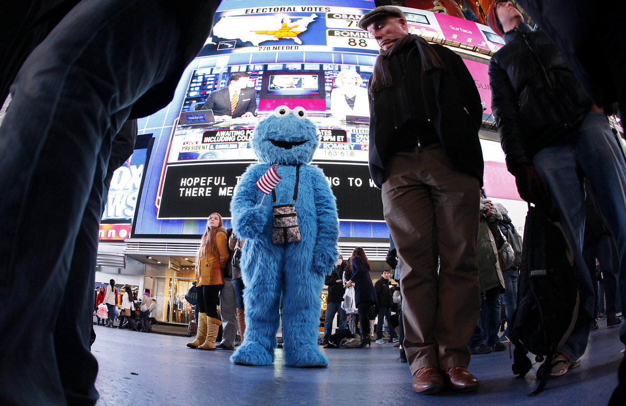 A man dressed as the character Cookie Monster watches TV screens in Times Square giving U.S presidential election results in New York November 6, 2012. [REUTERS/Carlo Allegri] PHOTOS: Full Focus - Election Day 2012