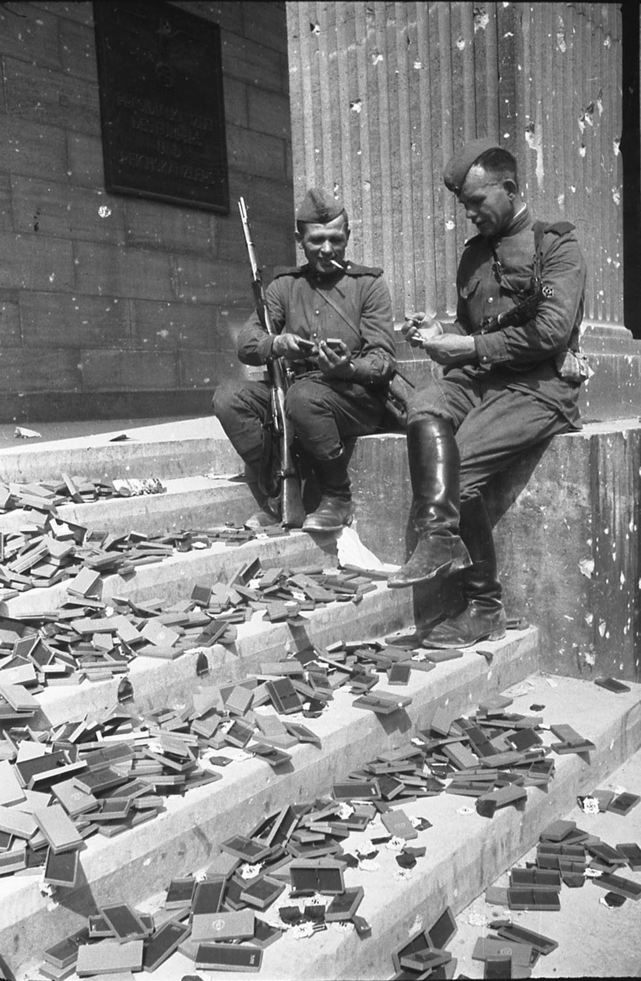 Soviet soldiers resting on the steps of the Reich Chancellery looking at German medals that have not yet been awarded, Berlin, by Evgeniy Khaldei, May 1945
