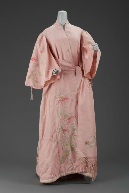 "Women's dressing gown by Iida Takashimaya, ca 1900 Japan (Kyoto, for the Western market), the Museum of Fine Arts, Boston  Pink silk taffeta dressing gown in kimono style with embroidered naturalistic chrysanthemums and butterflies in polychrome silks. Silk plain weave lining, padded hem and pleat in back of robe. Full sleeves gathered at shoulders and trimmed with braided silk cord and tassles. Matching sash of pink silk taffeta with double-sided embroidery of chrysanthemums in green brown and pink polychrome silk with knotted silk fringe. Gown labeled: S. Iida ""Takashimaya"" Silks and Embroideries. Kyoto."
