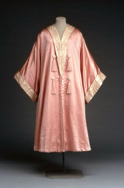 "Evening coat by Liberty & Co, 1900-25 London, the Museum of Fine Arts, Boston  Pink satin evening coat or wrap, cut in kimono style; collar and cuffs of white satin embroidered with pink silk in conventionalized floral design; lined with white satin. Front trimmed with white satin buttons wrapped with pink thread and pink tassels. Label: ""Liberty and Co., London and Paris"""
