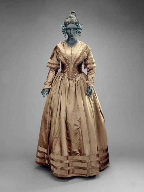 Dress, 1835-40 US, the Museum of Fine Arts, Boston  Woman's dress (a), alternate bodice (b), shoulder cape (c), and bow (d). Brown satin trimmed with piping, bands, bows, and pleating of same brown satin. Attached bodice trimmed with soutache braid of same color. Cape trimmed with long brown fringe. Both bodices have long sleeves. Very good condition.