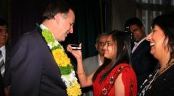 John Key looks at iPhone.