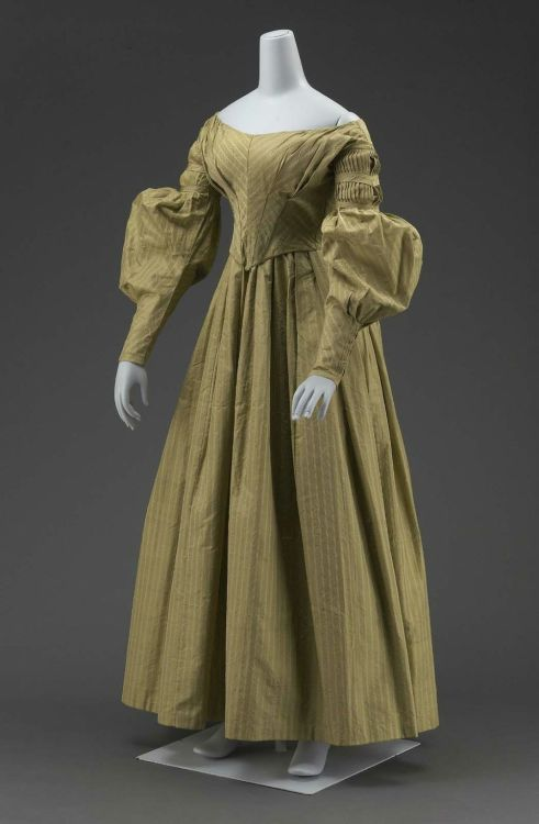 "Going away dress and matching cape, 1838 US, the Museum of Fine Arts, Boston Newly wedded couples change into ""going away"" outfits before leaving their reception.  This tradition is fading in most places, but it's still hanging on here in the South.  Dress (a) and matching cape (b) of grayish-olive-green silk with fancy-woven stripes with lines of white; fitted bodice, pointed in front; widely flaring neck; fullness across bust in unpressed pleats; long sleeves with fine pleats in upper part held in place by bias folds, full from just above elbow to above wrist, fullness pleated vertically to wrist; full skirt with loose pleats in front and gathered in back; short double cape (b) of same material with edges finished with bias folds of self material; both dress and cape fully lined with white cotton cloth; probably the going-away outfit of Harriet Maria Spelman, married to Estes Howe, August 20, 1838."