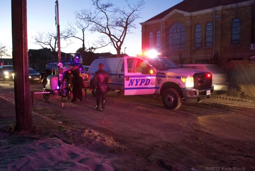 "NYPD haul their own 1000 gallon fuel tank in #Rockaway. Other than auto headlights, their safety light towers are the only source of illumination on the peninsula. They run on generators. Dark falls fast here. I left the church long before sundown, because I wanted to get back to the truck while I could still see obstacles in the walkways. The sand in the roads slowed me down considerably. In the time it would take me to walk a mile on the streets of my Brooklyn neighborhood, I had only managed seven blocks through streets which were now debris-littered sand dunes. Walking in the road would have been dangerous, as most of the auto traffic was from giant dump trucks with low visibility, long braking distances and not as much traction as they would have on streets not covered with sand. I stuck to the sidewalks, running under any trees with overhead branches. A man passed me and gruffly admonished me for not wearing a mask. I didn't have one, and my lungs felt it. Wind whipped dust and sand everywhere. I could feel the grit on my teeth.Dark started to fall. Really fall. Next to the road, car headlights gave some respite, but down every side street was a thick blackness.Ten blocks from where the truck was parked, National Grid workers had generator powered lights in the street. One of the workers approached me. He told me to put my camera away and rush to the other side of the peninsula. ""It's not safe here. ""See those streets down there? Bad things are happening there every night. Forget about taking pictures and get to the bay side. There's police activity there."" I shoved my camera inside my coat and crossed. I walked fast along the sidewalk, but the gravity of his delivery impressed me. Within arms length, shopgates twisted and opened into blackness. Probably the storm, but possibly looters. Glass doors left crackled and crumbled. I rushed to the center of the road to walk there. On the bay side, cars were gridlocked, trying to get back to the mainland. I had to get back on a sidewalk, back to walking alone in the dark. I considered knocking on car windows asking for a lift to the polling place. Just when I was about to give in, I could see lights up ahead. There were bright towers of lights over the polling place at 104th, and the soft red glow of the counter light at the food truck. Whatever bogeymen, real or imagined (or possibly FEMA), were lurking in the dark, they were back there. Here was light and heat."