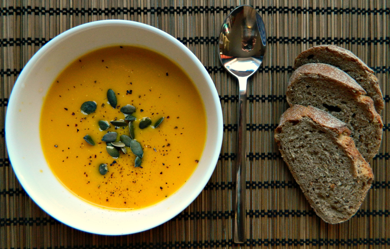 Carrot, Orange and Garlic Soup. (served with FGBP, pumpkin seeds and fresh rye and caraway bread.) Serves 2. This an incredibly cheap, easy and delicious soup! It's particularly warming in these winter months and is lusciously creamy. If you're not a garlic fan, sub in half of a yellow onion instead to make a just as tasty carrot and orange soup. 350g carrots (4 large carrots ~ish?); 500ml vegetable stock; 1 orange - juice and rind; 1 garlic clove; A drizzle of olive oil for the pan; Some milk - 100ml or so. (I used soya.) 1. Peel and top and tail the carrots, then roughly chop them in to bite size pieces. Mince the garlic. 2. Heat a large saucepan on a medium heat with the oil, then add the garlic and carrot, stirring to lightly coat. Leave for 3-5 minutes to soften slightly, stirring from time to time to prevent sticking. If this is the case, add a little more oil or some water. 3. Finely grate the rind of the orange, then slice the orange in half and squeeze the juice out of both halves. Add the rind to the carrot/garlic mixture, frying for another minute. 4. Add the vegetable stock to the pan and then leave to simmer for 15-20 minutes or until you can cut through a piece of carrot with relative ease. Add the orange juice at the last minute, then transfer everything to the blender and blend until smooth. 5. At this point, your soup will be quite thick. If you like it like that, then leave this step. If you want your soup to be creamier and thinner (and for it to go further), then heat up your choice of milk in the saucepan, transferring to the blender once warmed through and blend again. 6. Enjoy! Fresh parmesan would be lovely with this or a light, crisp spinach salad. If you're as much of a garlic fiend as myself, then mix together some softened butter, minced garlic, salt, pepper and dried basil in a small dish then spread this over toasted bread to get very simply but effective garlic toast.