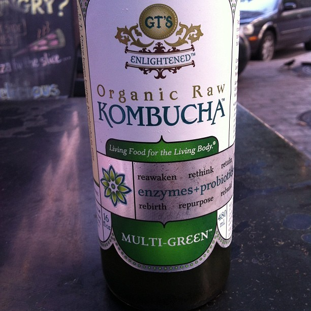 I'm drinking GT's Organic Raw Kombucha: Multi-Green. #paleo #nomnom. While the guy to the left of me is drinking a Mountain Dew. #toadwins