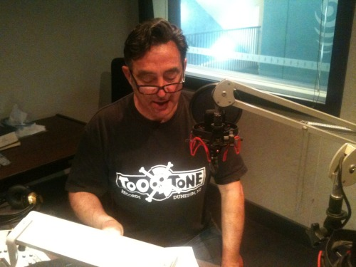 Reading the poem  'There' on RNZ this aftn in Two Tone Record Shop Dunedin T-shirt. #poetryactionshot