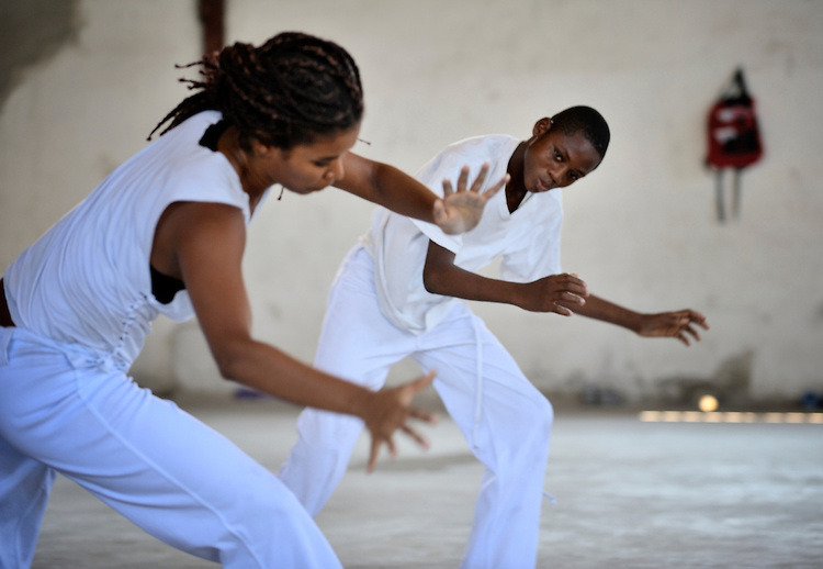 A Brazilian instructor helps Haitian children learn Capoeira, an Afro-Brazilian fighting style, at a community center in the Bel-Air neighborhood of Port-au-Prince, Haiti. The program is sponsored by Viva Rio!, a Brazilian organization helping to revitalize the neighborhood..  COPYRIGHT:Paul Jeffrey