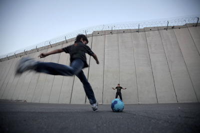 fotojournalismus:  Palestinian children play football in front of the Israeli separation barrier in the West Bank village of Abu Dis on November 8, 2012. [Credit : Ahmad Gharabli/AFP/Getty Images]