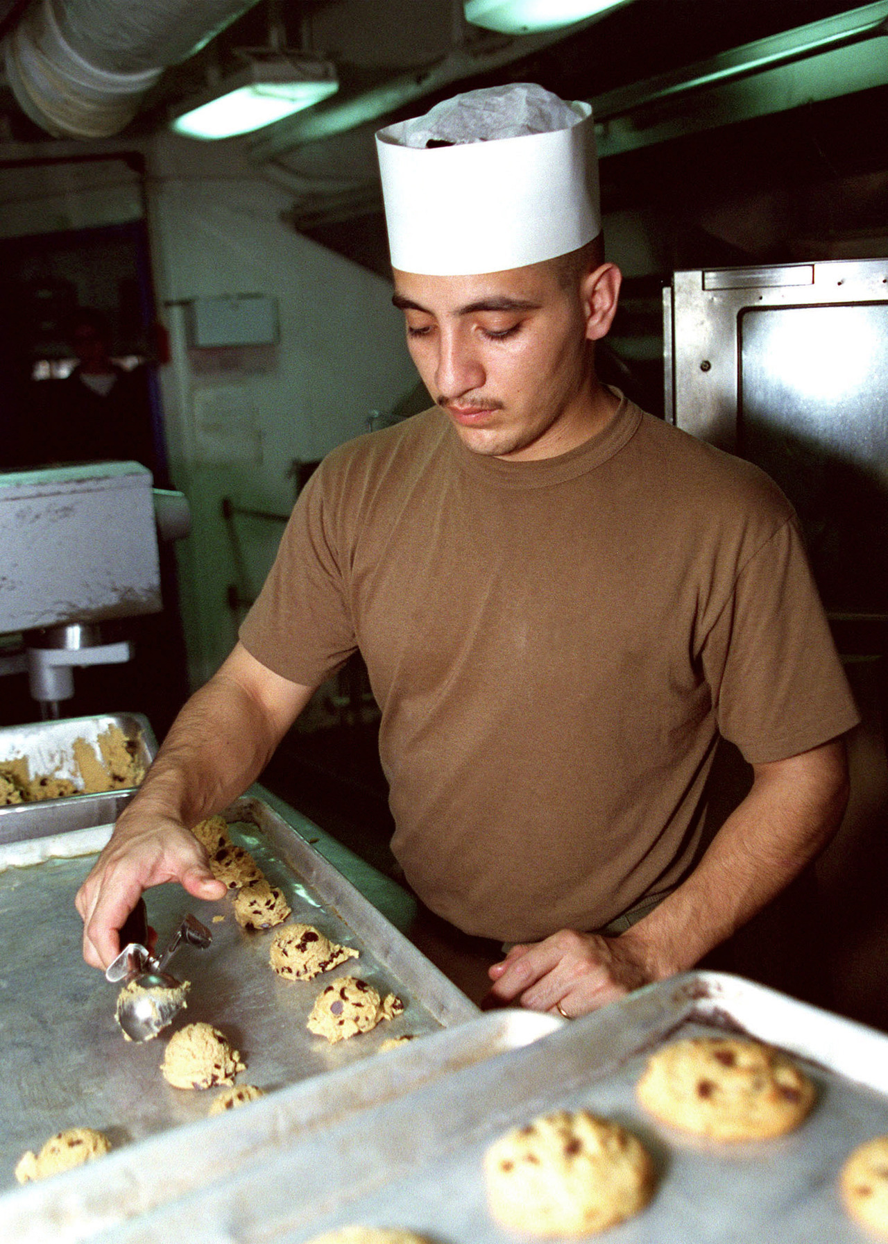 December 4th is National Cookie Day!   U.S. Marine Corps CPL. Victor Medrano prepares chocolate chip cookies for the crew of the aircraft carrier USS NIMITZ (CVN 68). Nimitz is deployed to the Persian Gulf in support of Operation Southern Watch, 01/29/1998