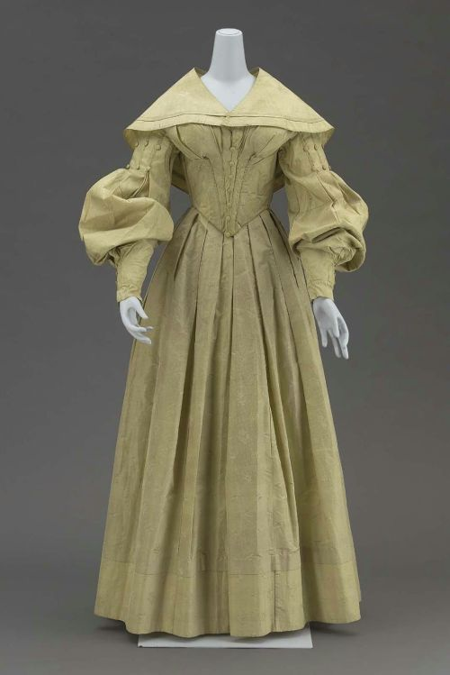 Wedding dress and matching cape, 1839 US (New Hampshire), the Museum of Fine Arts, Boston  Dress worn by Elizabeth Richards at her marriage to John S. Parmelee in Newport, New Hampshire, January 19, 1839. Wedding dress of light gray green figured silk having all-over small dot and powder of two different stylized blossoms; bodice fitted and boned coming to V at waistline at center front, hooked down center back, bodice front trimmed with folds of self material and row of self covered small buttons, V neck, leg-of-mutton sleeves with top fullness caught down by lines of piping and self covered buttons, skirt full all the way around with fullness in pleats in front and on sides, in gathers center back; (b) matching short round shoulder cape; bodice lined with unbleached heavy cotton twill; skirt faced with cream colored cotton, and cape lined with cream colored cotton.