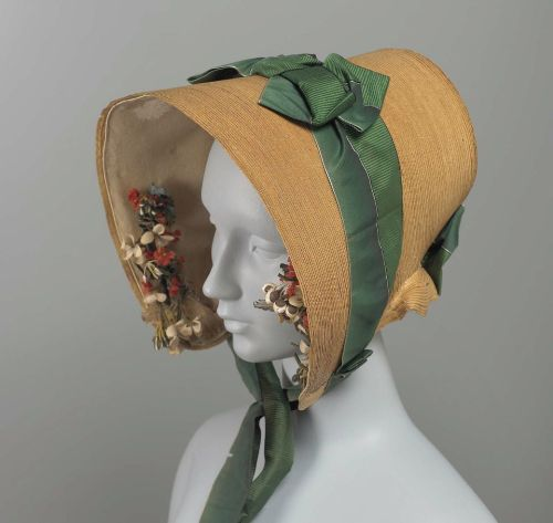 Leghorn bonnet, ca 1840 US, the Museum of Fine Arts, Boston  Yellow leghorn; brim and crown in one piece; designed so that brim frames face closely; short cape of leghorn, trimmed with green ribbon divided down back so that one half is ribbed and the other half ombré; brim lined with cream colored georgette crepe; cluster of artificial flowers including white violets, on each side of brim facing.
