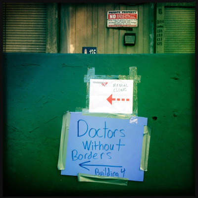"Photo: MSF set up an emergency clinic in Far Rockaway, NY, for Hurricane Sandy relief. © Michael Goldfarb/MSF Far Rockaway: Global Disaster Zone (originally posted on Outside) Days after Hurricane Sandy hit New York, vast relief effort led by city, state, and federal agencies was under way, but the affected area was so widespread that many people, particularly along the poorer, low-lying margins of the city, felt forgotten and abandoned by their government. MSF set up an emergency clinic with a volunteer staff of a dozen or so doctors, nurses, and assorted health professionals. A folding table was piled high with medical supplies, and a sheet strung up in a corner created a makeshift private screening area. An empty Starbucks jug doubled as an ad hoc sharps disposal container. Misha Friedman, a Moldovan photographer in his thirties with a shaved head—a veteran of Doctors Without Borders missions from Sudan to Uzbekistan—was briefing a pair of volunteers about the dire health situation faced by 800 senior residents in a nearby housing complex who had had no running water or electricity for a week. ""No one's been evacuated,"" he told me. ""There is no evacuation. Doctors have been flooded out, pharmacies have been closed. Some patients are on dozens of medications, and they kind of fall off the grid."""