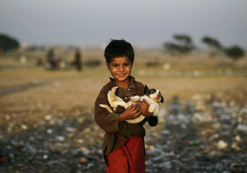 politics-war:  Afghan refugee boy Samiullah Afsar, 5, carries a puppy he found in a pile of a garbage, on the outskirts of Islamabad, Pakistan. Photo: Muhammed Muheisen