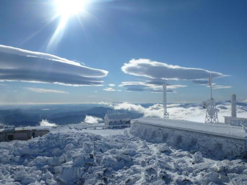 Breathtaking view from Mount Washington Observatory, looking toward the southeast. Floating lenticulars dot the sky while rime ice and snow blanket the summit landscape.