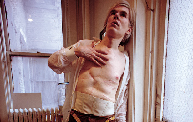 theswinginsixties:  Andy Warhol showing scars from his shooting in 1968. Photo by David Montgomery.  I like to think of it as her shooting.