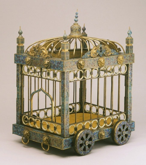 18th Century Dog Cage This elaborate dog cage epitomizes the luxurious life of the imperial court during the long reign of the Qianlong emperor, when the extravagant display of wealth extended even to the accouterments of the imperial kennels. The body of the cage is decorated with the intricate enameling technique known as cloisonné … The finials at the top of the cage as well as the five-clawed dragons and lions' heads around the perimeter are gilded, and rows of jade rings complete this miniature palace on wheels. The emperor was said to be especially fond of cloisonné and had workshops that specialized in the process established on the palace grounds in Beijing, where this cage for a favorite pet dog was undoubtedly fabricated. Felice Fischer, from Philadelphia Museum of Art: Handbook of the Collections (1995), p. 34.