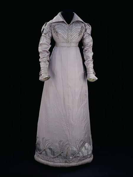 Walking dress, 1817-20 UK, the Victoria & Albert Museum    Echoes of military uniform give this walking dress a masculine flourish. The curving satin bands applied to the front of the spencer are reminiscent of the parallel lines of braiding which extended across the breast of many uniforms. Passementerie in the form of crescent-shaped moulds, looped cord and balls covered in floss silk replace the gilt or silver buttons on some regimental coats. The tassels on the collar ends and cuff bands evoke the tassels adorning boots, hats, sashes and cap lines of military accessories. In place of epaulettes, puffed oversleeves composed of linked bows emphasize the shoulder line. The infusion of military styles into fashionable dress in Britain was largely due to the influence of the Napoleonic Wars (1793-1815). Among other factors, contact with foreign troops had a strong impact on civilian as well as regimental dress, and military ornament was translated into stylish trimmings on women's hats, bodices, spencers and pelisses. The uniforms worn during this period were some of the most elaborate in the history of military dress, and their bright colours, frogging, braid and tassels fuelled the imagination of fashion for years to come. Although this walking outfit is not based on any particular uniform, some garments closely followed certain styles. The uniform of the hussars, who were light cavalry, was particularly flamboyant as it was derived from Hungarian national dress. In her memoirs, Elizabeth Grant describes the admiration she received when she 'walked out like a hussar in a dark cloth pelisse trimmed with fur and braided like the coat of a staff-officer, boots to match, and a fur cap set on one side, and kept on the head by means of a cord with long tassels'.