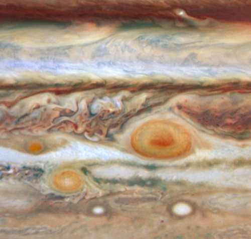 Jupiter's Spots     In what's beginning to look like a case of planetary measles, a third red spot has appeared alongside its cousins — the Great Red Spot and Red Spot Jr. — in the turbulent Jovian atmosphere.      This third red spot, which is a fraction of the size of the two other features, lies to the west of the Great Red Spot in the same latitude band of clouds.      The new red spot was previously a white oval-shaped storm. The change to a red color indicates its swirling storm clouds are rising to heights like the clouds of the Great Red Spot. One possible explanation is that the red storm is so powerful it dredges material from deep beneath Jupiter's cloud tops and lifts it to higher altitudes where solar ultraviolet radiation — via some unknown chemical reaction — produces the familiar brick color.      Detailed analysis of the visible-light images taken by Hubble's Wide Field Planetary Camera 2 on May 9 and 10, and near-infrared adaptive optics images taken by the W.M. Keck telescope on May 11, is revealing the relative altitudes of the cloud tops of the three red ovals. Because all three oval storms are bright in near-infrared light, they must be towering above the methane in Jupiter's atmosphere, which absorbs the Sun's infrared light and so looks dark in infrared images.      Turbulence and storms first observed on Jupiter more than two years ago are still raging, as revealed in the latest pictures. The Hubble and Keck images also reveal the change from a rather bland, quiescent band surrounding the Great Red Spot just over a year ago to one of incredible turbulence on both sides of the spot.      Red Spot Jr. appeared in spring of 2006. The Great Red Spot has persisted for as long as 200 to 350 years, based on early telescopic observations. If the new red spot and the Great Red Spot continue on their courses, they will encounter each other in August, and the small oval will either be absorbed or repelled from the Great Red Spot. Red Spot Jr. which lies between the two other spots, and is at a lower latitude, will pass the Great Red Spot in June.      Full Photo Description