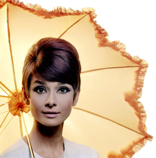 A publicity photo of Audrey Hepburn posing with a yellow parasol for the movie How to Steal a Million.  Photograph by Douglas Kirkland at the Studio de Boulogne. Paris, France, November 1965.