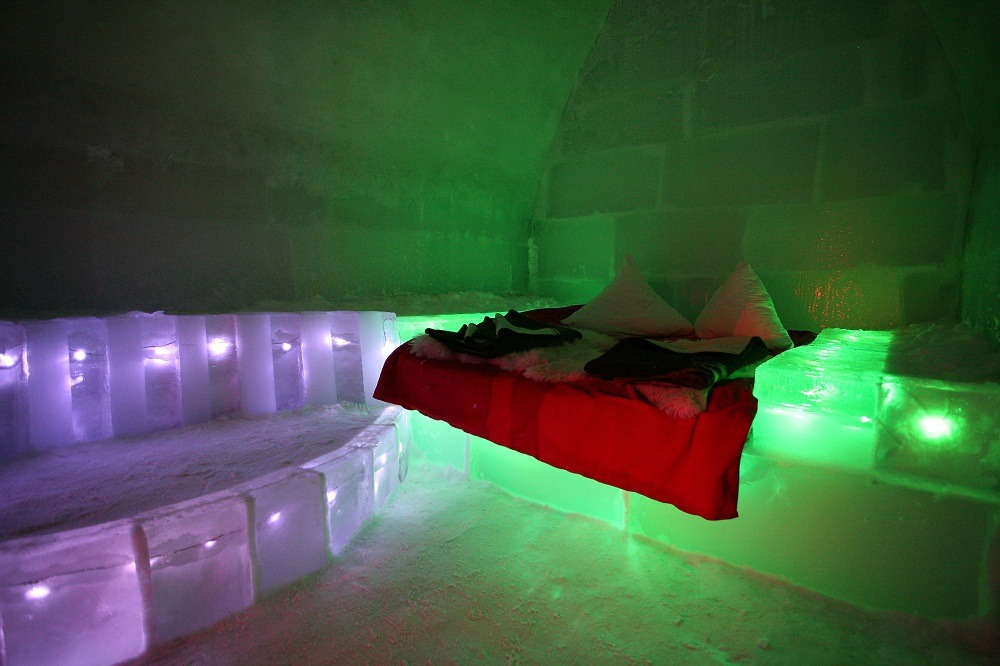 Ice Hotel - Balea Lac, Romania Standing at 2000m above sea level, between the icy peaks of Fagaras Mountains, the remote Ice Hotel can only be accessed in the winter via cable car. The hotel is hand carved each year by local craftsmen using traditional techniques, this way each corner of the hotel is unique and re-designed every year. All rooms are individually sculpted and feature ice beds covered with insulating reindeer fur then topped with mattresses for extra comfort. The colored lights embedded into the ice creates a magical atmosphere when lit up at night.