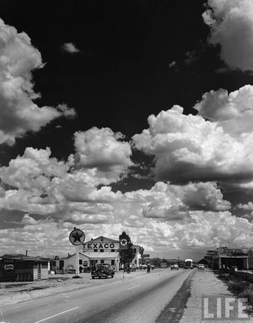 thepieshops:  AMERICAN CITIES Dramatic cumulus clouds billowing over a Texaco gas station along a stretch of highway US 66, aka Route 66). Location: Seligman, AZ, US Date taken: September 1947 Photographer: Andreas Feininger