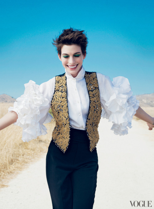vogue:  Anne Hathaway in a Ralph Lauren Collection gold-embroidered vest with beading, linen blouse, and wool trousers.Photographed by Annie Leibovitz See the slideshow  This shot is perfection. The colour of the sky, the contrast with her jade eye make up the white sand the crisp white shirt, the gold detail of the waistcoat and the golden long grass in the background. It's just good.