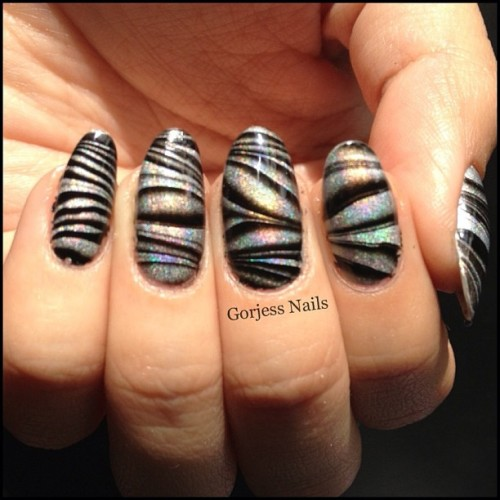 This #watermarble is supposed to resemble #zebrastripes. #holographic #nailart #zebranails They're more holographic in real life!!