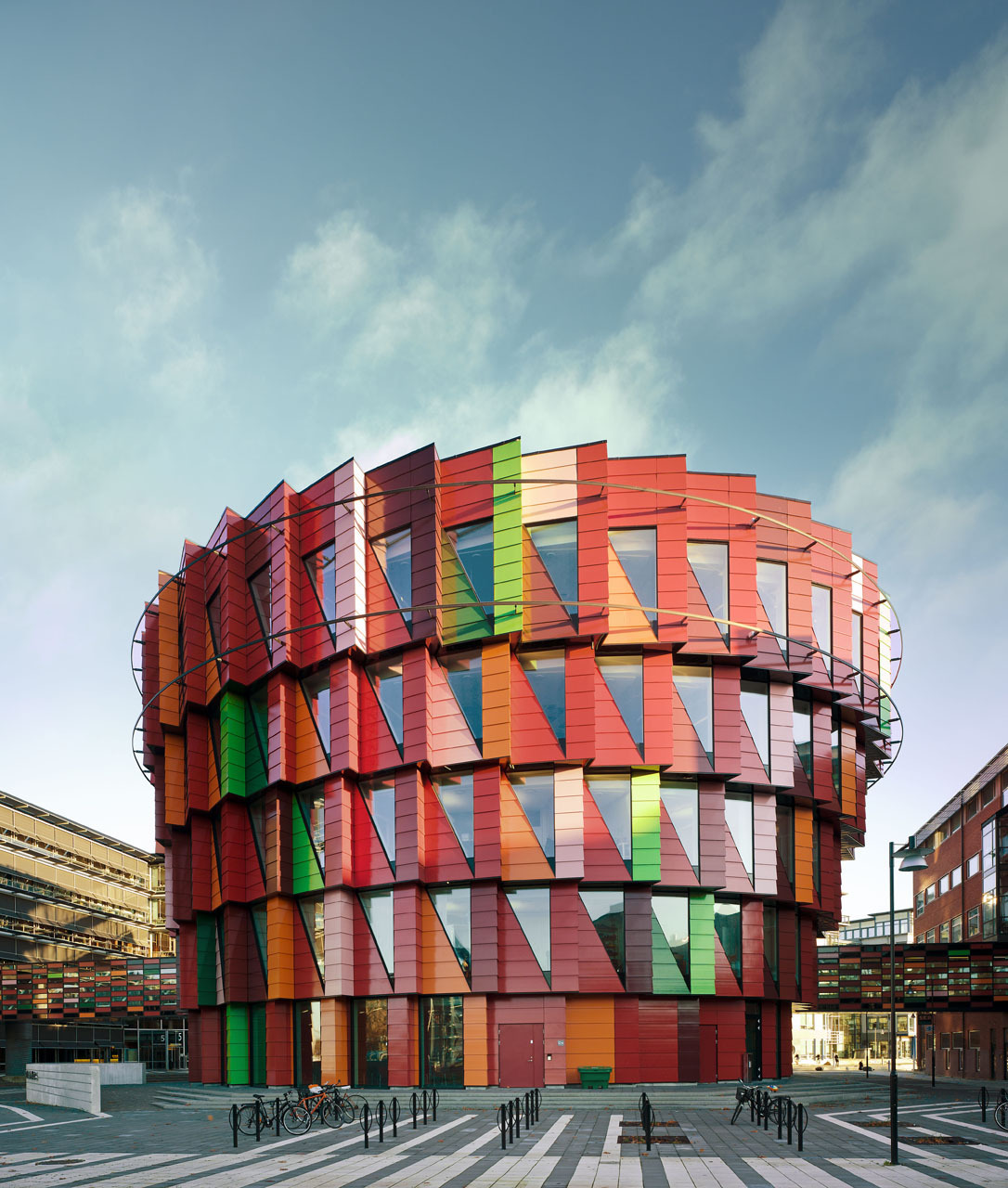 "Kuggen Office ""A cylindrical, distinctive building in the middle of the town square is an urban planning motif with roots in the Italian Renaissance. The form offers lots of floor space in relation to the amount of exposed exterior wall surface, and the upper floors project out over the lower—more on the south side than on the north, so that the building partially shades itself when the sun is high in the sky. A rotating screen shades the top floors, following the sun's path around the building."" See more:  http://www.archdaily.com/289791/casa-a5-csa-arquitectura/"