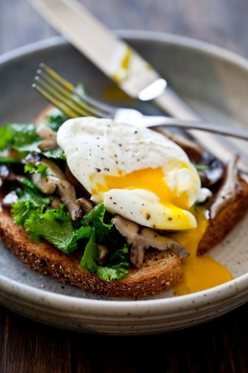 Mushroom & Wilted Greens Toast with a Poached Egg 2 slices whole wheat or multi-grain bread 2 tbsp. olive oil 1 large clove garlic, minced 2 cups sliced mushrooms – you can use any variety you prefer 4 cups chopped greens, tough stems removed – you can use mustard greens, kale or chard here 1/2 teaspoon grainy Dijon mustard 2 large eggs 1 tsp. white vinegar salt and pepper, to taste - Toast (using your favorite method) the bread and go ahead and arrange each one on its own plate. - In a medium sized skillet, heat the oil over medium heat until faintly shimmering. Add in the minced garlic and saute until soft but not brown – 1 to 2 minutes. Add in the mushrooms, stir to combine and cook until they begin to release water. Throw in the chopped greens and stir again to get everyone mixed up. Stir in the bit of mustard and allow the greens to cook until tender but not mushy – 2 to 3 more minutes. - Meanwhile, fill a medium sized soup/stock pot with water and bring to a boil. Add in the vinegar. With the end of a spatula or spoon, stir the water vigorously in a clockwise motion to create a swirl. Drop the cracked egg into the water and form slightly with your utensil. Cook for 2-3 minutes or until the white is solid around the yolk but not to soft-boiled egg stage. Using a slotted spoon or small screened scoop, remove the eggs from the water. - To serve, divide the greens mixture into two and top the toasted bread with it. Place a poached egg on top of the mixture. Season with a bit of fresh ground pepper and serve immediately – the joy of this is the runny egg so be speedy in serving & eating it. Serves 2.