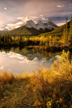visitheworld:  The Three Sisters reflected in the lake near Canmore, Alberta, Canada (by Michael James Imagery).