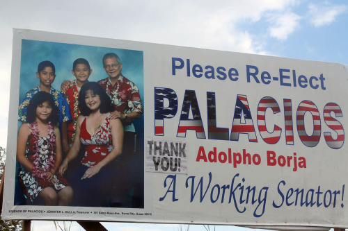 sumahi:  2012 Guam Political Sign Awards: Best Family Award - Adolpho Palacios  It's becoming more and more common to include family members in political signs. It is only a matter of time until political signs start to look like the stock family photos that come in your picture frames. This election the Best Family Award goes to Senator Adolpho Palacios. His family of five is dressed in beautiful red, white and blue Hawaiian print shirts. They are smiling and warm and appear to not just be a Senator's family, but also perhaps a musical family from the 70's that drive around Guam in a red, white and blue van and perform at village fiestas! In their spare time I imagine them solving mysteries as well.