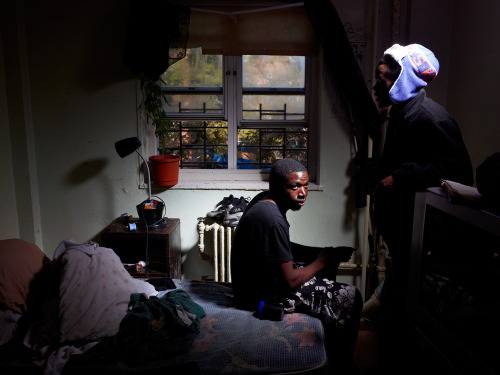 "timelightbox:  Elijah Jones, 23, sits in his room on the fourth floor of the Redfern Houses. Since the storm, water has condensed on the walls and ceiling because his room is so cold, and mold is starting to grow on his walls. Every day he tries to clean the moisture from his room, but the water keeps coming back. ""That's the only light we got,"" he says pointing to a spotlight on a generator in the courtyard. ""We just got that like three days ago."" (photo: Finlay MacKay for TIME ) For many in Sandy's path, the storm itself was terrifying. On Staten Island, houses collapsed, crushing people underneath; in Breezy Point, families fled blocks of homes in flames. But in Redfern, the real struggle began the next day, when it became clear that power wouldn't return for weeks. See more photos here."