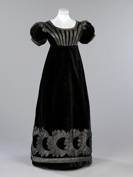 Mourning evening dress, 1823-25 Scotland, the Victoria & Albert Museum    This black velvet evening dress was worn Jane Johnstone (1803-1847), niece of William Jardine founder of Hong Kong merchants Jardine, Matheson & Co. The wide neckline and short sleeves of the dress are typical of fashionable evening wear of the mid 1820s. Although it retains remnants of the high-waisted, neo-classical shape popular at the beginning of the century, its construction shows the move towards the lower waists and fuller skirts of the 1850s. The use of velvet demonstrates the trend for more sumptuous fabrics after the dominance of cotton and muslin in the previous two decades. The death of Princess Charlotte, the only child of George IV, in childbirth in 1817 plunged the whole country into mourning and set the high standards for mourning dress of this period. Fabrics such as silk and velvet were too shiny to be worn for the first stages of mourning, however, official mourning guidelines issued by the Lord Chamberlain decreed that black velvets and silks were permissible in the third and final stage. This dress would have been worn with an evening turban, long gloves and a pelisse cloak, often lined with chinchilla fur. It is likely that it was a gift from William Jardine and was worn when mourning the death of Jane Johnstone's grandmother, Elizabeth Johnstone who died in 1825.