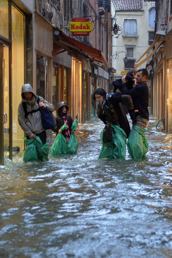 Venice submerged by record-breaking floodingA family wading through a flooded Venetian street wear trash bags around their legs to keep dry on Nov. 11 during an 'Acqua Alta' in Venice. In some areas of Venice, the flood water has reached 5 feet — the 6th highest level since records began in 1872. This is the 4th time since 2000 that Venice has been submerged by record high flood water. See more flood photos.