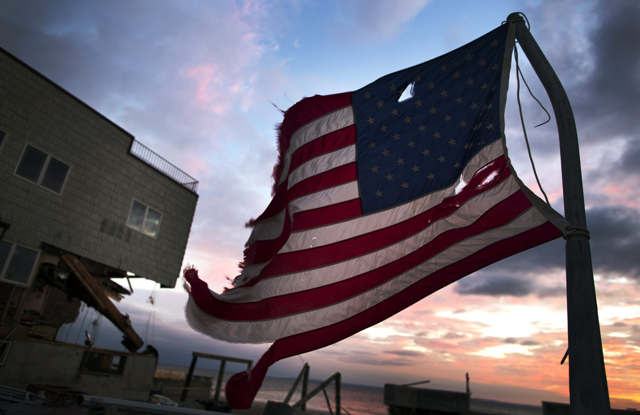 From Hurricane Sandy: The Long Recovery, one of 45 photos. A tattered flag flies at sunset on a pole in front of a home damaged by hurricane Sandy in the Brooklyn borough neighborhood of Seagate, on November 13, 2012. (Reuters/Lucas Jackson)