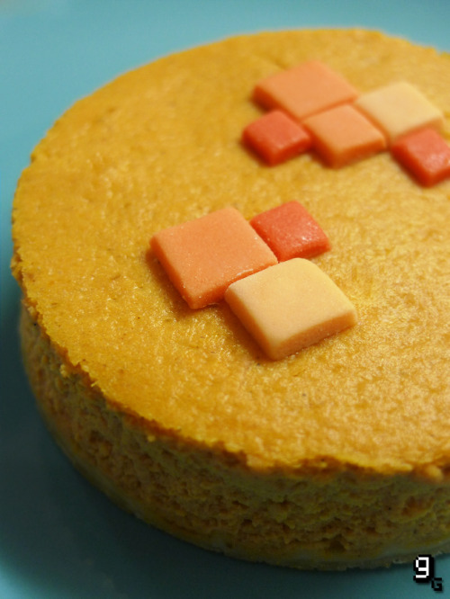 gourmetgaming:  Request: Minecraft – Pumpkin Pie  Someone was kind enough to remind me that it is Thanksgiving soon! Here in the UK we don't celebrate the holiday, nor do we eat enough sweet pumpkin flavoured things if you ask me, so I was very, very excited when I saw Minecraft had recently added Pumpkin Pie. This recipe is a bit of a hybrid between a traditional pie, a cheesecake and delicious edible pixels. I promise this is the last recipe of the year that is orange and involves pastry, because it took me 4 attempts to get it just right this time. Not quite as simple as the input made it appear… This recipe makes 2 small Pumpkin Pies. What you will need: A 9-inch loose base cake tin, a large bowl, a whisk/electric mixer, and a 3.5 inch round cookie cutter. Ingredients: 150g / 6 oz Shortcrust Pastry [Recipe] 150g /⅔Cup Light Brown Sugar ½ Teaspoon Ground Cinnamon ½ Teaspoon Ground Ginger ⅛Teaspoon Nutmeg Pinch of Salt 400g / 2 Cups Cream Cheese (Room Temperature) 3 Large Eggs (Room Temperature) 1 Teaspoon Vanilla Extract 1 Tablespoon Maple Syrup 230g / 1 Cup Canned Pumpkin To Garnish: Various shades of orange icing, cut into small squares. Preparing the Pumpkin Pie: Preheat the oven to 200C/390F. With your pastry prepared, roll it out to about 1cm thick, and cut a piece to line the base of your cake tin. Bake it in the oven for 12 minutes until golden, then remove and leave to cool. Once it's out of the oven, turn the temperature down to 180C/355F. Meanwhile, combine the light brown sugar with the cinnamon, ginger, nutmeg and salt. In a separate large bowl, beat the cream cheese until smooth. Gradually add the sugar and spices, while continuing to beat the cream cheese. Next add the eggs, vanilla and maple syrup and mix well. Stir in the pumpkin and mix again until combined, then pour the mixture over the now cooled pastry. Place a small tray of water in the bottom of the oven to keep the air moist. Put the pumpkin pie in the middle of the oven to bake for 30 minutes. After 30 minutes, change the temperature of the oven to 160C/320F and bake for another 15 minutes. Once firm, remove the pumpkin pie and leave to cool before placing in the fridge to chill for several hours, or overnight. Making the Pumpkin Pie: Remove the pumpkin pie from the cake tin and place on a flat surface. With the cooking and chilling, the filling will have contracted. Take a large round cookie cutter, and cut two perfect cakes from the large cake. Decorate each of the pumpkin pies with tiny icing pixels, and serve with some freshly whipped maple cream.  Beautifully creamy, fluffy and light with a crisp base – I'm feeling hybrids in baking are the way to go. I loved the sweetness with the spices, and then the unusual taste of pumpkin was really complimented by the gentle sour of the cream cheese. While I have no prior pumpkin experience, it was pretty delicious and something I'd like to bake into more cakes in the future for sure. Like this? You might also enjoy the Castlevania: Symphony of the Night - Cheesecake.