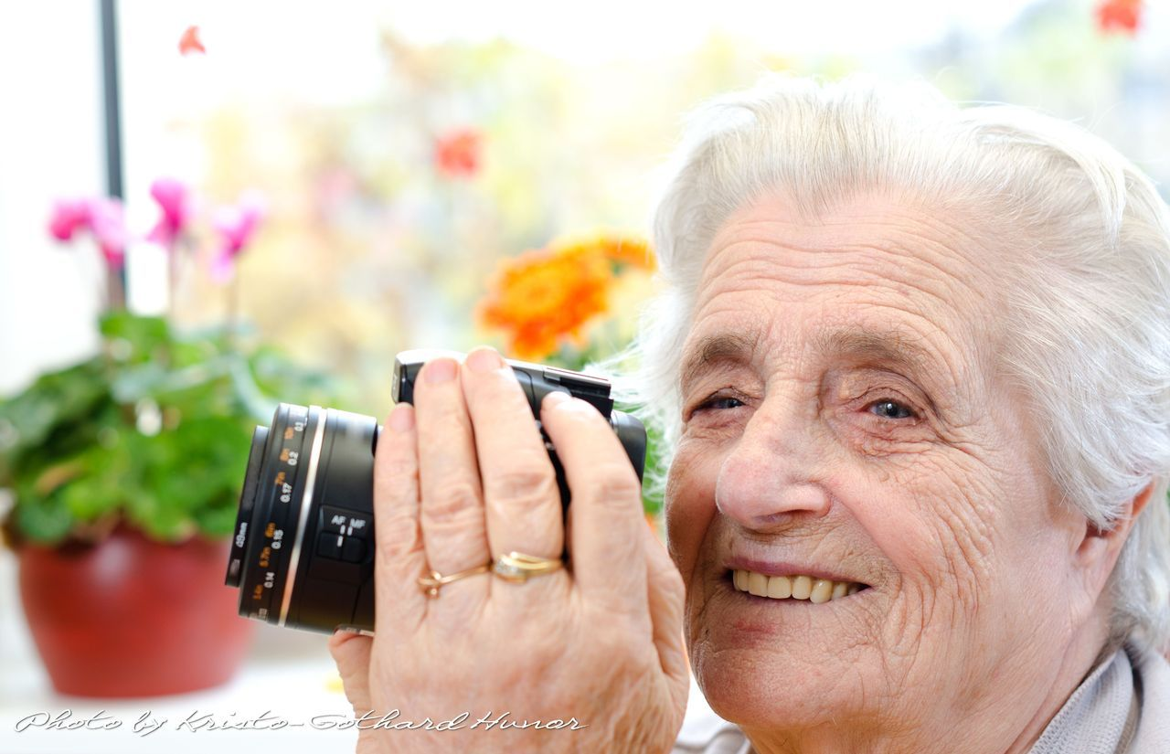 Old woman taking photos at home