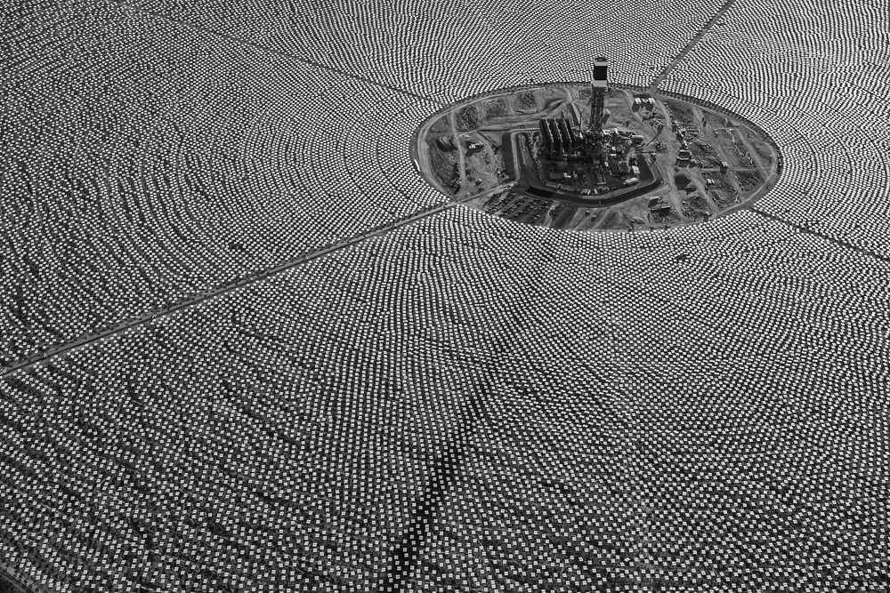 Aerial view of Solar Field One at the Ivanpah Solar Electric Generating System (ISEGS) on October 27, 2012. Photo shows completed tower construction and heliostat (pairs of mirrors) installation. Mojave Desert, CA.  One big problem with renewable energy projects is that they have to go somewhere. They have to occupy a part of the very environment that their proponents are often trying to save. Photographer Jamey Stillings beautifully captures this tension in his images of the Ivanpah Solar Electric Generating System (ISEGS). Located in Southern California's Mojave Desert, the plant aims to eventually be the largest solar thermal power plant in the world – making enough electricity to run 140,000 homes all by focusing the sun's energy to create steam.
