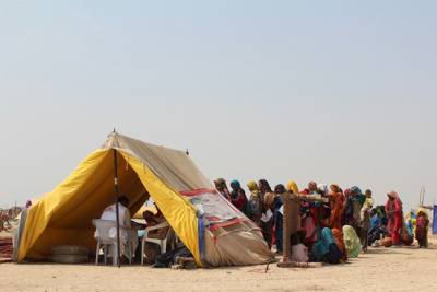 "Photo: Patients queue for medical attention outside an MSF tent at a mobile health clinic and ambulatory therapeutic feeding center in a camp for people displaced by the floods in Dera Murad Jamali. Pakistan 2012 © Fathema Murtaza Voices From the Field: ""There Are Thousands of Families Who Lost Their Homes Because of the Floods""  Amina's StoryAmina*, mother to a one-month-old baby boy, shares her story on how her child came to be admitted to MSF's hospital in Dera Murad Jamali. Her son was brought to the MSF nursery when he was 10 days old; weighing only 2.36 kilograms [about five pounds] he was diagnosed with tetanus. ""I have been married for two years; this little boy is my first child. I haven't named him yet—I was not sure if he would survive. I like the name Yaseen, maybe that will be his name.  We have no shade, no home or land; we live on the side of the road and use our beds as a tent. I delivered him under a makeshift tent near the Pat Feeder Canal. There are thousands of families who lost their homes because of the floods and are now living there too. My husband, Saeed*, used to work on our landlord's land. But the water came; it was shoulder high and we lost everything, even the food we had stored is lost. Our landlord came down from Karachi to ensure the water was drained from his land so we could return to it. We don't have anything to rebuild with and the landlord gave us nothing. He has gone back to Karachi. We are still hopeful that we will get some help. When my son got sick, I pawned my earrings because we had nothing left to pay the doctors, however, when we came to the hospital here, we were told the treatment in the hospital is free! So, I used the money from the earrings to buy food for our family instead. It's been a month since I sold my earrings, and now even the food is gone. A few days after my son was born, he started having fits and had a temperature. We went to a private clinic where they said they couldn't help us, but told us that we should take our son to the MSF hospital because they have a lot of facilities. So we brought him here. My son has been here for 25 days now. Before I brought my son to the hospital he was not drinking any milk; he wasn't even able to cry. He is my first child. I worry about him—and wonder if he will survive. We had thought about taking him from the hospital and going home because we didn't see an immediate change in his health at first.Now, though, he opens his eyes. The nurses have explained that my son can be treated and can now slowly start to feed.  Change has happened. My son is better. Now we are going to be patient and let the medical staff tell us when our son is ready to leave. I am very relieved and happy to see my son getting better. When I am able to take him home, I plan to celebrate by providing food to people who are poor and less fortunate than my family and me. We may not have anything, but at least we have our son. 'Only Allah can help us now.' We are glad we were able to access such good health care, and we know that it has saved our son. *Names have been changed to protect patient's anonymity."