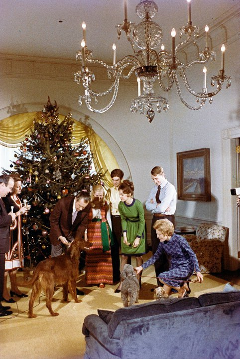 The Nixon family with their dogs Vicky, Pasha, and King Timahoe around the Christmas tree in the White House residence.  L-R, President Richard Nixon, Pat Nixon, Julie Eisenhower, David Eisenhower, Tricia Nixon Cox, and Ed Cox.