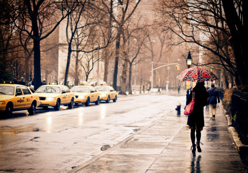 "nythroughthelens:  Rain. New York City. Greenwich Village. When the sky opens up over the city, urban wanderers glide over the surface of streets slick with shadowy memory. And every drop of rain holds the world in its slippery grasp. —- Recently, someone who saw this same photo in black and white inquired if I also had the image available in color. Since I shoot in color and convert my color photos to black and white after the fact (with a few exceptions), I went through my library and found my color rendition of this scene. I was struck with how the photo evoked a different set of emotions when viewing it in color. I have come to love it in black and white to such an extent that my memory of the scene as it occurred also plays out in my mind in black and white. However, I remember the initial appeal of this candid moment was the strong bursts of color against the winter-bare trees. The day was bitterly cold: the type of damp cold that seeps down to the bone and in one short moment, the street erupted with color. It was such a fleeting moment but it created such a spark. On a related note, I read an interesting essay by Joel Meyerwitz a few days ago on the New York Times Lens Blog called A Question of Colors - Answered. Meyerwitz is part of a current exhibition in London which compares some of Henri Cartier-Bresson's black and white images with work by other noted photographers who have been influenced by him but have chosen to work in color for a large part of their photography careers. The curator of this particular exhibition states that: ""This exhibition will show how Henri Cartier-Bresson, in spite of his skeptical attitude regarding the artistic value of colour photography, nevertheless exerted a powerful influence over photographers who took up the new medium and who were determined to put a personal stamp on it. In effect, his criticisms of colour spurred on a new generation, determined to overcome the obstacles and prove him wrong."" It's interesting to me that color photography inhabits a more defensive realm than black and white photography especially when it comes to street photography. I think that both have different psychological effects on the viewer. However, both can be just as valid in terms of having artistic value. However, it's definitely not a simple debate. —- View this photo larger and on black on my Google Plus page —- Buy ""Autumn - New York City - Overlooking Union Square"" Posters and Prints here, View my store, email me, or ask for help."