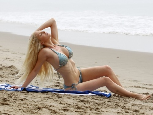 Heidi Montag flaunted her curvaceous bikini bod on Wednesday as she seductively played in the sand! See her entire photo shoot on our site here!