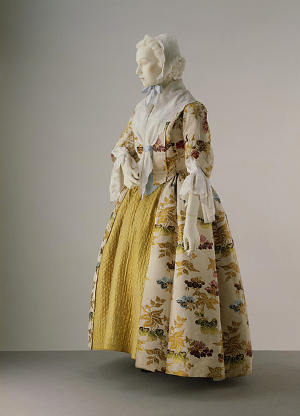 Formal day dress, ca 1735 England (Spitalfields) (altered 1740's and 1780's), the Victoria and Albert Museum  By the 1730s the open robe was beginning to replace the mantua as formal day wear. The beautifully patterned Spitalfields silk indicates a degree of luxury. The accompanying quilted petticoat suggests that the ensemble was probably worn for afternoon tea parties rather than in the evening at the opera or theatre. The pattern of the silk, with pear-shaped fruits and exotic flowers, is typical of the 1730s. The gown itself was altered in the 1740s and probably again in the 1780s.