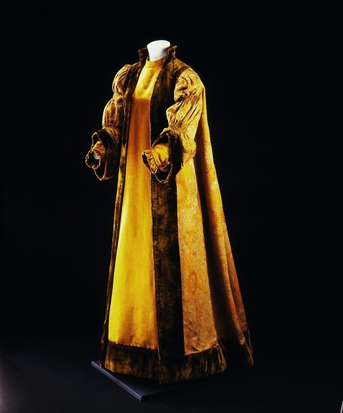 Robe by Liberty of London, ca 1897 London, the Victoria & Albert Museum    Object Type This garment with its full sleeves and long, flowing silhouette owes much of its inspiration to Pre-Raphaelite dress. The gown consists of a flared front panel attached to an open, flowing robe which falls from pleats at the back. The front panel has a patch pocket on the right side which is hidden by the deep plush edging. Materials & Making The puffed sleeves, wide cuffs and velvet edgings are inspired by plain, loose 16th century gowns. The sunflower and pomegranate motif on the fabric was a recurring design on objects associated with the Aesthetic Movement. The subtle gold and brown tones were popular 'artistic' colours used in both dress and furnishing fabrics during the 1890s. People Pre-Raphaelite painters had clothed their models in plain, loose dresses based on the forms of 'early Medieval art'. The opening of Liberty's dress department in 1884 helped popularise the taste for aesthetic dress. The Liberty designs which ranged from aesthetic gowns and children's artistic dresses to more conventional 'tea-gowns' had a wide international appeal among the social elite. Ownership & Use This type of dress was seen as the healthy and aesthetic alternative to the corseted and constrictive fashions in conventional dress. Before long it was not only those with artistic leanings who chose to wear garments which fit more loosely. By the early 20th century many fashionable dresses had a softer shoulder line and a more natural silhouette.